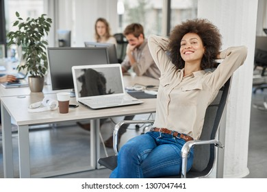 Mixed race female CEO smiling and sitting in chair with hands behind head. In background employees working.