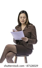 Mixed race female reading  a sheet of paper. She is sitting and holding telephone.This has clipping path