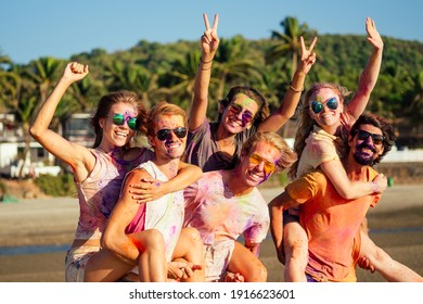 mixed race friends having fun with colors on seaside outdoors in Goa India