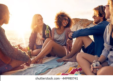 Mixed race friends having fun at the beach. Group of happy young people sitting together at the beach talking and drinking beers.