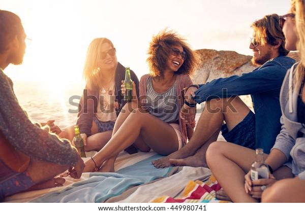 海辺で楽しい雑種の友達。ビーチで一緒に座って話したり、ビールを飲んだりする幸せな若者のグループ。