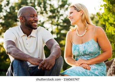 Mixed race friends talking to each other at a park on a summer day