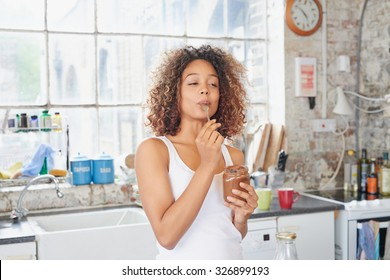 Mixed race girl indulging cheeky face eating chocolate spread from  jar using spoon savoring every  mouthful