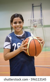 Mixed race girl playing basketball on court