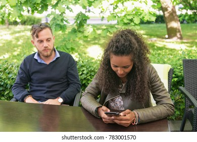 Mixed race girl surfing at her mobile phone while her boyfriend looking at what she is doing. At street cafe. Vilnius, Lithuania