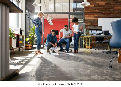 Mixed race group of creative people meeting in the office and discussing. Creative people looking at project plans laying on floor of modern workplace.