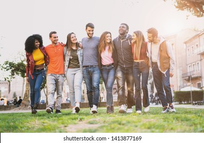 Mixed race group of friends having fun walking outdoors hand on shoulders. Young people community walking together. Integration and diversity concept.