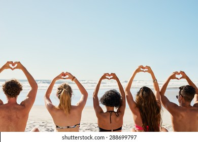 Mixed race group of friends making heart shapes with hands raised up to the sky show a love of summer and sunshine shot from the back