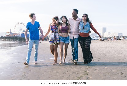 Mixed race group of friends walking in Santa monica beach. Happy smiling people having fun together on the beach