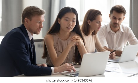 Mixed race groups of employees sitting at shared table, working on different projects. Focused middle aged team leader or executive manager showing financial calculations to young chinese coworker.