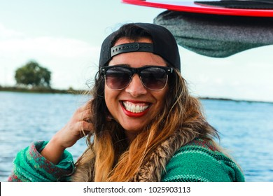 Mixed race happy young woman smiles and poses on a boat during a day on the lake