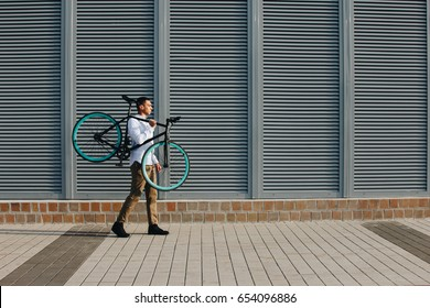 Mixed race hipster man carrying bicycle on shoulder in the city