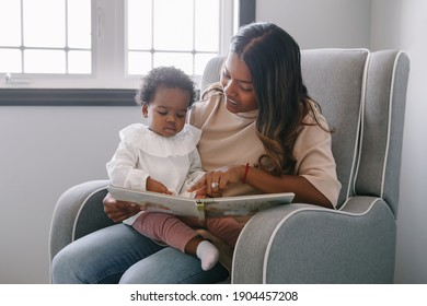 Mixed race Indian mom reading book with African black baby girl toddler at home. Early age children education development. Family authentic candid lifestyle.