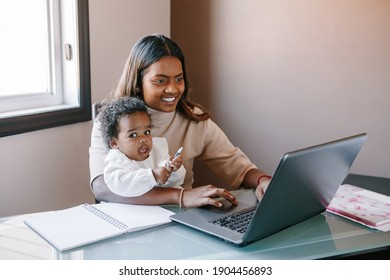Mixed race Indian mother with African black baby working online from home on Internet. Workplace of freelancer woman with kid. Stay home single mom working distant job. New normal.