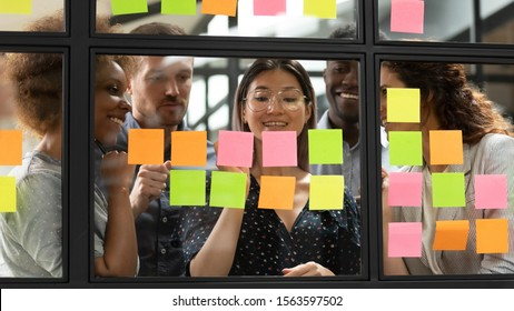 Mixed race interested young managers group gathering near smiling vietnamese team leader, writing startup project details or tasks on colorful sticky notes, using kanban scrum methodology at office.