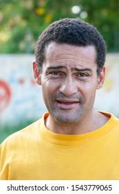 mixed race man in the neighborhood, walking on the street, lifestyle portrait