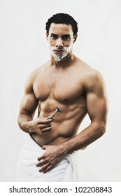 Mixed Race man in towel shaving