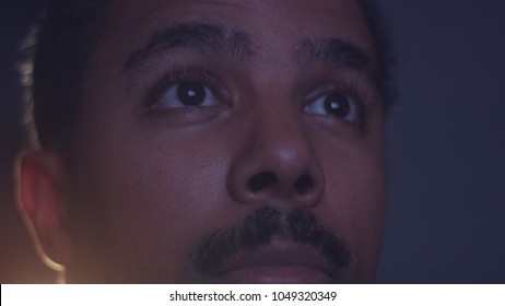 mixed race man watching tv in darkness with different color light from tv on face. Eyes closeup