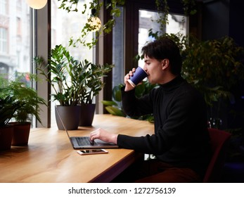 Mixed race man working with laptop and smart phone at cafe. Green plants at background.