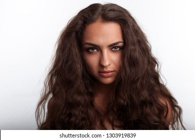 Mixed race model with hair like lion mane. Very furry hair. Portrait of pretty young woman with long curly wavy brown hair.