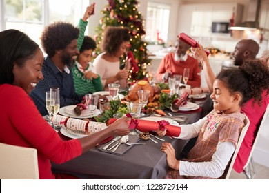 Mixed race, multi generation family having fun pulling crackers at the Christmas dinner table