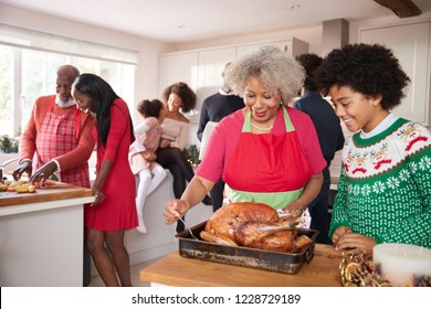 Mixed race, multi generation family gathered in kitchen before Christmas dinner, grandmother and grandson preparing roast turkey in foreground