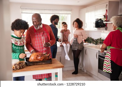 Mixed race, multi generation family gathered in kitchen before Christmas dinner, grandfather and grandson preparing roast turkey in foreground
