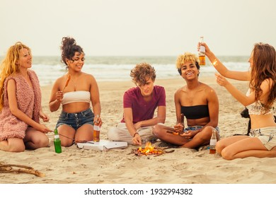 mixed race multinational group of friends cooking sausages and drink lemonade at sunset on sand
