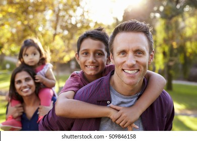 Mixed race parents carry kids piggyback, selective focus
