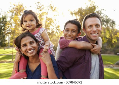 Mixed race parents carry their kids piggyback in a park