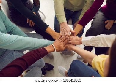 Mixed race people sitting in circle and putting hands together in business team meeting or group therapy session. Community, trust, success, motivation, mutual responsibility, unity, support concepts