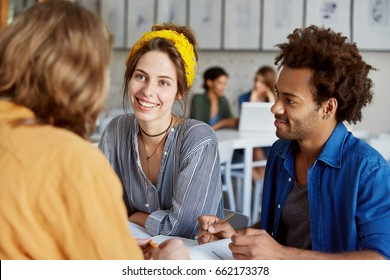 Mixed race people sitting in classroom having brainstroming writing something with pencils being indoors. Friendly students doing home assigment together after classes helping each other with pleasure