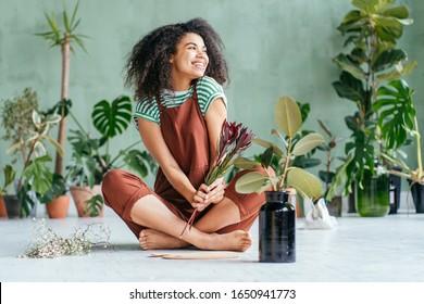 Mixed Rennen spielfu Frau sitzend auf Bodengartenarbeit zu Hause. Pflanzen zu Hause wachsen. Pflanzliche Mutterbegriff Frau, die Hauspflanzen anbaut.