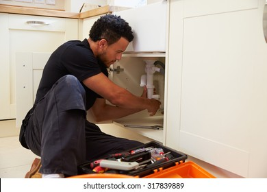 Mixed race plumber fixing the kitchen sink in a home