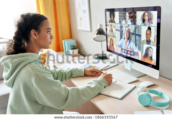 Mixed race teen school girl college student distance learning during virtual remote class, group online lesson on video conference call with teacher on computer screen studying at home by videocall.
