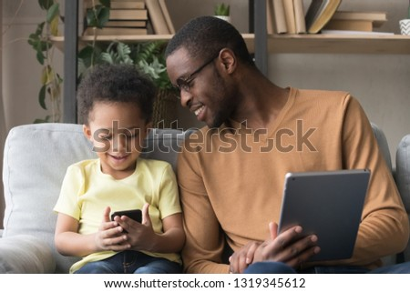 Mixed race toddler child son and black father using gadgets sitting on sofa at home, african dad with cute little kid boy holding digital tablet phone having fun, family devices technology concept