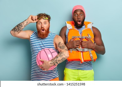 Mixed race two men stare at camera, shocked witness emergency situation on water. Surprised redhead bearded man wears goggles and striped t shirt, holds beach ball, Afro man in lifejacket and swimhat