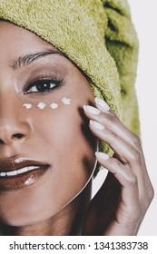 Mixed race woman is applying eye cream on skin. Wrinkles treatment.