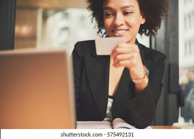 Mixed race woman in coffee shop using credit card for paying