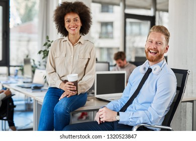 Mixed race woman holding coffee to go and sitting on the desk while CEO sitting in chair. Both looking at camera.