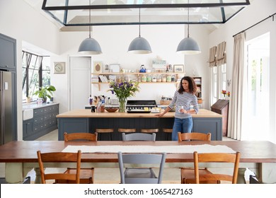 Mixed race woman leaning on kitchen island in open plan home