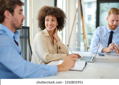 Mixed race woman listening to coworker and using laptop while sitting at table on meeting. Start up business concept.