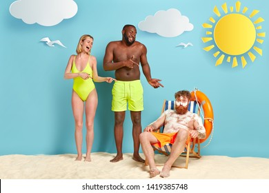 Mixed race woman and man laugh at funny friend covered with white burn cream, has sunburnt skin after lying in sun for long time, sits at beach chair. Red haired male applies sunscreen on skin