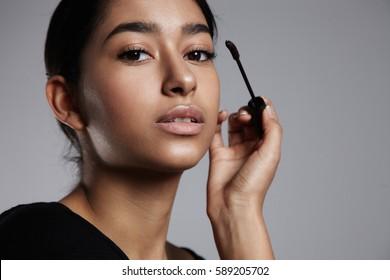 mixed race woman with mascara during makeup process