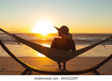 Mixed race woman on beach holiday sitting in hammock during sunset. healthy outdoor leisure time by the sea. - Shutterstock ID 1952122297