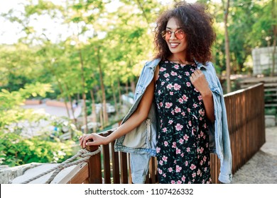 Mixed race woman with perfect teeth and Afro hairs spending her leisure in park . Close up portrait of cute lady in pink sunglasses and jeans jacket.