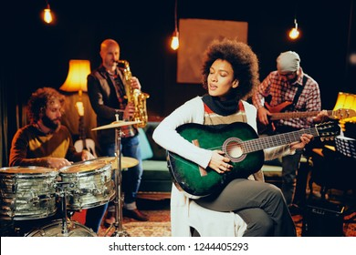 Mixed race woman playing acoustic guitar and sitting with legs crossed in home studio. In background the rest of the band playing drums, saxophone and bass guitar.