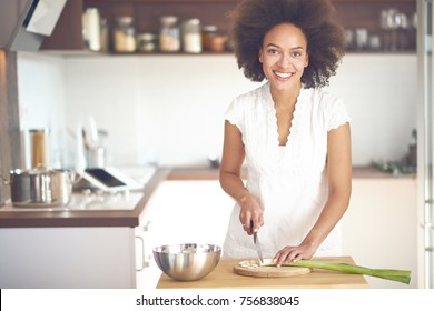 Mixed race woman preparing dinner. Chopping leek while standing in the kitchen