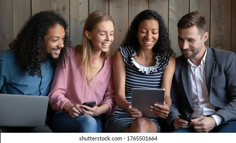 Mixed race woman showing funny video, interesting website to diverse friends sit in cafe spend time together. Multiethnic friendship, modern tech usage, 5g fast internet, have fun with buddies concept