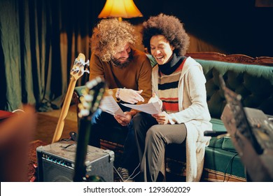 Mixed race woman sitting on the sofa with her Caucasian friend and looking in home studio.